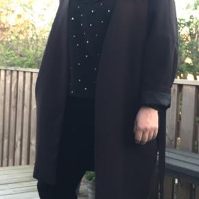 Sort kimono agtig jakke med bindebånd i taljen. På ærme opsmøget kan man se at jakken er tyndt foret, ligesom en blazer.