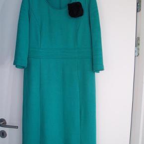 Varetype: Kjole Størrelse: 14 Farve: Grøn  Talje 42 cm x 2 Bryst 46 cm x 2 Længde 104 cm.     Lynlås i siden.     Blomsten er ikke til salg    Der er ikke for i kjolen    98 % bomuld og 2 % elastan