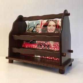 """Skøn ældre retro magasinholder i robust lakeret træ sælges.  Mål: H. 37 cm. B. 23 cm. L. 43 cm.  For at give en fornemmelse af dens størrelse, har jeg placeret den ved siden af en spisebordsstol i """"standard"""" størrelse.  Den har få almindelige brugstegn.  Pris: 150,-kr.  Er til afhentning.  Se også mine mange andre ting og sager😊- klik på mit navn for at se alle mine ting."""