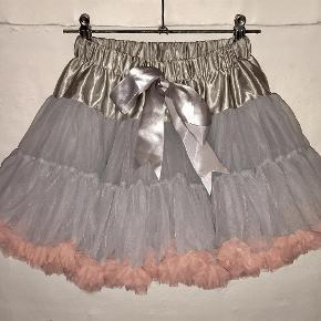 Varetype: Tylnederdel / strutnederdel Farve: Grå og rosa  Flot nederdel med mange lag tyl og meget strut. Der står str. 120 i nederdelen, men vurderer den svarer til ca. 128. Målene er: Talje ca. 2x25 cm (kan med rimelighed strækkes til 2x30cm) Længden er ca. 35 cm.  Brugt 1-2 gange, hvis den overhovedet er brugt. Standen er som ny.  Fra røg- og dyrefrit hjem.