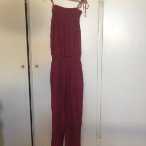 Rigtig flot buksedragt i smukt print. Aldrig brugt. Der er lommer i.  Man kan bruge bindebånd som stropper eller gemme dem væk.