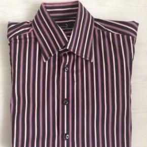 Super smart herreskjorte fra Selected med lodrette striber i flotte lyserøde, sorte og hvide farver.  Gennemknappet foran samt en knap ved håndleddet - ekstra knapper medfølger.  Bærer overhovedet ikke præg af brug.  Fremstillet af bomuld.  Vaskes på 40 grader.