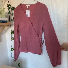 💗CLOSET CLEANOUT💗 Smuk slå om bluse / binde bluse fra H&M i lyserød / hindbærfarvet 🌸 Den er aldrig blevet brugt, og fejler intet - ny og stadig med prismærke :) den er str. 36 💕  Kommer fra røgfrit hjem 💘