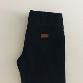 Wrangler denim jeans i sort. W34L30, men kan også sagtens fitte w33. Har let frynsede ender