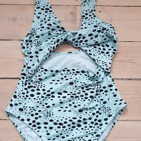 Flot lyseblå leopard badedragt med cut out under brystet str 38  Den er brugt en gang, fremstår flot og næsten som ny  den sælges for 180kr kan sendes med postnord for 20kr som alm. brev eller med DAO for 37,50kr