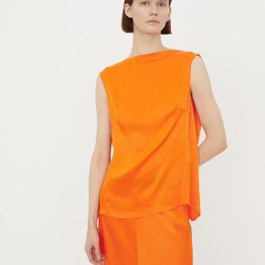 Lækker og blød satin bluse i en kraftig orange. Blusen er ærmeløs oh har en bådudskæring foran, som går ned i et en dyb V-udskæring i nakken. Den har et løst fit med brystindsnit, som skaber form til barmen.   100% Viscose   Nypris 1600,-   Bytter ikke!