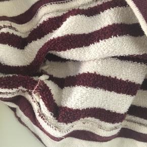 Dejlig sweater der holder dig varm med offwhite og bordeaux striber.  Størrelse S fra Moss Copenhagen.  Er brugt meget lidt og fejler derfor intet. Spørg endelig efter flere billeder.  Kom med et bud. Mængderabat gives ved køb af flere dele.  Sender gerne på købers regning.