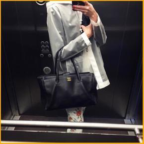 """Så elegant Chanel Cerf Tote Bag i sort kalvelæder med guld hardware. Tasken er den store høje model og er perfekt som hverdagstaske, da den kan rumme en MacBook 13"""" og har masser af rum og lommer, til at holde orden i ens ting. Den har et stort åbent rum bagpå, to indvendige rum med lynlåslukning, et aftageligt stort stofrum med lynlås og et stort rum foran. Tasken lukkes med en kraftig magnet. Prøv eventuelt at søg på 'Chanel Cerf Tote Bag' på YouTube: her er flere videoer, hvor de forskellige rum og detaljer af tasken bliver beskrevet og vist.  Tasken er i det lækkreste kalveskind, som er afvisende over for snavs og ridser. Indvendigt har det sort for i stof. Den kan bæres på flere måder: henover skulderen i hankene, som håndtaske, med medfølgende rem som cross-body og med medfølgende rem som skuldertaske. Remmen har aldrig været brugt og er derfor fuldstændig ny og intakt.  Tasken har været brugt sporadisk i løbet af nogle år og aldrig dagligt (i gennemsnit 4 gange om måneden) og er blevet passet så godt på og opbevaret forsigtigt, og har få brugstegn. Læderet fremstår i SÅ fin stand og næsten som nyt, dog har det lidt slid i kanterne.Det sorte stof for indvendigt er også super fint, og kun med små brugstegn primært på det indvendige mærke. Noget af guldet yderst på 'stagen' af logoet er også blevet en smule falmet (se billeder). Sender gerne flere billeder ved oprindelig interesse.  Købt i vinteren 2013 i Chanel butikken i Hamborg. Original pose, kvittering, dustbag og carte d'authenticite medfølger.  Mål:  Bredde: 35 cm Højde: 24 cm Dybde: 15 cm Hanke: 22 cm høj Medfølgende strop: 94 cm (fuld længde)  Modellen koster fra ny $3,200.00, svarende til ca. 20500 kr.   MP: 15.000 kr.  Bytter ikke. Kan ses og mødes og handle i København V. Handler via bankoverførsel. Hvis du gerne vil købe, men ikke betaler med det samme, forbeholder jeg mig retten til at sælge til en anden side i mellemtiden, hvis du bliver overbudt. Sælges kun hvis rette pris opnåes."""