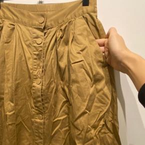 Beige nederdel med knapper og lommer, mega fin med strik eller skjorte nu. Den trænger til og blive strøget men ellers er den så god som ny ☺️
