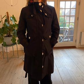 Superflot regnfrakke med klassisk trenchcoat snit og en dejlig rummelig hætte.  Regnfrakken har fine detaljer som skjult lynlås, hvide knapper samt bindebælte i taljen og binde bånd i hætten for optimal pasform.