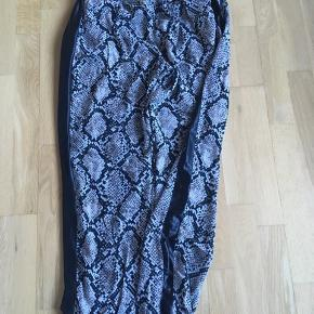 Fine loose bukser i dejligt tyndt stof med snakelook og sort strib ned langs siderne. Lommer i begge sider.