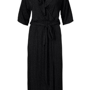 Knælang kjole, i sort med lodrette syninger med glimmereffekt. I taljen har kjolen elastik og et bindebånd. Kun brugt en enkelt gang.