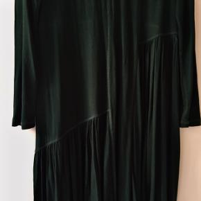 Kun brugt en gang Kjole i elastisk stof i mørkegrøn med flotte sømme-detaljer.  Sidder tæt på arme og overkrop. Drapperinger får selve skørtet til at falde flot.   Kan sendes med DAO for 36kr