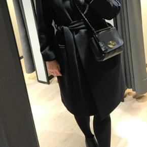 Super fin og klassisk sort frakke.   Har bindebånd og nogle ikke-synlige knapper. To lommer foran - en på hver side.   Brugt men stadig super fin og klar til en ny ejer.  Nypris var 2.200 kr og modellen hedder Livia og forhandles fortsat.