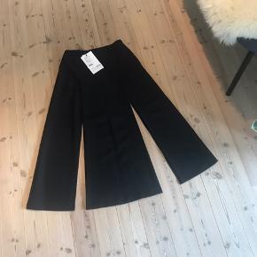 Spændende nederdel fra Selected People, i kraftigt stof, med dybe/lange slidser. Længen er ca. 10-15 cm over mine ankler ( jeg er 177cm høj)  Aldrig brugt