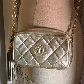 Guld metallic vintage Chanel kamera taske i blødt kalveskind med en lækker guldbelagt tung Chanel kæde. Str 17x10x5 cm. Almindelige brugsspor. Chanel box medfølger. Har nr i tasken - den er fra 1991-1993.