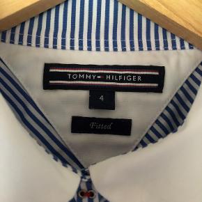Flot stribet Hilfeiger skjorte i fitted pasform. Blå og hvid stribet med logo kontrast ved knaplukningen.  Brugt nogle gange - fejler intet. Nypris kr. 700,-  Sælges afhentet eller plus porto for kr. 150,- Bytter ikke.