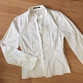 Virkelig skøn Hugo Boss skjorte i lækker skjortekvalitet i str. S/36. Med smal bindesnor om ryggen, skjult knaplukning foroven og smukke plisserede detaljer. Lille slids i ærmerne og logo på knapperne. Flot både åben og helt lukket.   Har kun været brugt ganske få gange og fremstår som ny. ✨ Den er lige det mindste til mig og billederne på er derfor ikke de bedste. Sælges kun fordi jeg er gået op i en M og denne svarer til S.   Mindstepris 200+fragt 😊