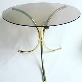 Lille rundt bord på messingstel med løstliggende glasplade i røgtopas. Hverken glasplade eller stel er særlig tungt. Mål: H: 51,5 cm. Ø: 60 cm.