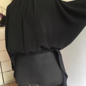 Smuk elegant sort blusekjole, der sidder til med elastik i taljen, hvor den er kort fortil som en bluse og lang bagtil som en kjole. Blusedelen har vide ærmer, og kjoledelen har split.  Flot tynd strukturvævet crepe chiffonstof, som dog er tæt vævet, så lys lige kan anes igennem, men den er ikke gennemsigtig.  Str. 38, som kan passe en str. M og L, da størrelsen er så fleksibel. Lynlås på ryggen, så den er nem at tage på.   Pris ved afhentning i Nordsjælland ellers + porto.