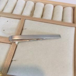 Enkel sølv slipsenål fra Randers Sølvvarefabrik.   Måler i længden 6,5 cm og er o,5 cm bred.   Overfladen er materet, hvilket giver et pænt og maskulint udtryk.   Skriv for flere billeder eller oplysninger.