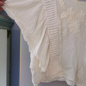 Smuk Zara top i creme hvid med blonder og lidt puffede korte ærmer. Blusen er en anelse cropped og god til jeans og nederdel. Derudover er der knapper ned af ryggen. Str. M. BRUGT, men stadig fin.