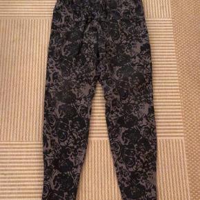 Zizzi lækre grå mønstrede bukser i strækstof med elastik i taljen str S. Måler i livet 95 cm, når der strækkes let i elastikken. Matr 97 % bomuld og 3 % elastan. Kan strækkes til 104 cm i taljen.