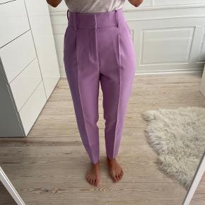 Højtaljede lilla/violette pæne bukser fra Zara i str XS. Bukserne er som nye. Sælges da jeg ikke får dem brugt. Sælges for 120 kr. Kan afhentes i Kbh K eller sendes med dao til pakkeshop. Jeg giver mængderabat ved køb af flere ting - se mine andre annoncer