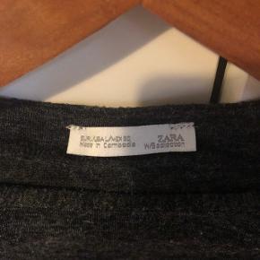Tynd trøje fra Zara i mørkegrå-meleret materiale med bindebånd. Lille i størrelsen - passer en S-M Byd gerne 🌸
