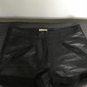 Varetype: læder shorts Farve: Sort  Fede shorts i blødt lammeskind. Med lomme og lynlås på begge lommer.     De er foret med et bomulds for.    Brugt men i fin stand.    Køber betaler porto og gebyr. Handler gerne mobilepay.