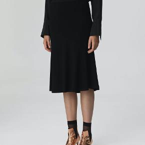Denne Tassia nederdel er fremstillet i en let stretch-blanding og skåret på skrå for at give stylen et let draperet udtryk. Nederdelen er forsynet med et kontrastfarvet, elastisk taljebånd for den optimale pasform. Materiale: 82% viscose, 16% polyamide, 2% elastane.  Nypris: 1200kr.