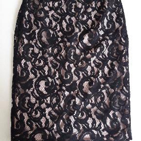 Flot sort blonde pencil skirt i silke.  Underskørt i en lækker rosa farve der ses gennem blonden.  Str s.  God stand.  Mål: 57 cm lang - talje 71 cm - hoftemål 89 cm.