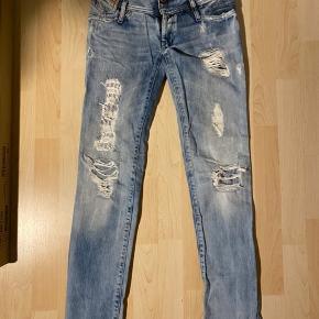 Lækre lavtaljede diesel bukser i str 25/32. Bukserne er flittigt brugt, men grundet den kraftige kvalitet, fremstår de stadigvæk i rigtig fin stand.   Bemærk venligst hullet lige under lommen på bagsiden. Hullet er en del af designet på bukserne, men nogle af trådene er knækket, og derfor er hullet mere tydeligt nu.