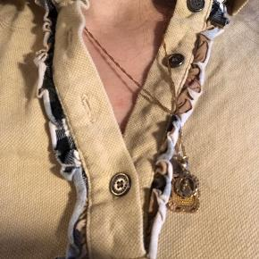 Cute polo agtig trøje i beige fra Burberry med broderet logo. Har flæsekant med det klassiske ternede mønster i hvid, brun, sort og rød. Desværre mangler den en knap for oven. Måske du kan fikse og finde en der ligner, jeg har brugt den uden og har ikke haft betydning for mig.