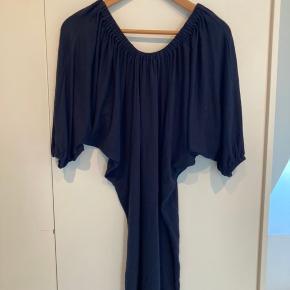 Fin mørkeblå kjole med flagermusærmer. Sidder til forneden og falder fint over brystet.