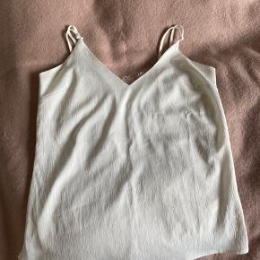 Sælger denne fine hvide top med flot mønster brodering på ryggen. Der er dog to små sorte/brune pletter foran. 50kr plus porto