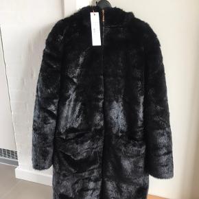 Lækker jakke i sort kunstpels fra Sofie Schnoor. Stadig med prismærke. Nypris kr. 1999. Længde fra skulder ca. 95 cm. Længde ærme indvendigt mål ca. 46 cm. Kan sende flere billeder, hvis det ønskes.