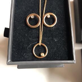 Smykkesæt bestående af halskæde med vedhæng i form af lille halo ring med en lille zirkonia sten i. Matchende øreringe medfølger.  I guldfarvet (/ved ikke om det er forgyldt). Fra Pilgrim.  Stand: næsten som nyt. Ørestikker har været i brug få gange og halskæden lidt færre gange.  OBS: smykke æske haves desværre ikke, men jeg sender det i en smykkepose fra Pilgrim, naturligvis godt pakket ind. Husker ikke NP.  150,- + fragt / TS Dao kr. 37,-  Bytter ikke.