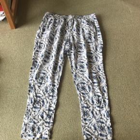 Blomstrede løse bukser med elastik i taljen og bindebånd. De har lommer. Str.Xl men passer også en Large.  Sender gerne - køber betaler fragt  BYD