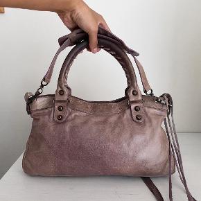 Lidt om tasken 👜 Balenciaga the first skuldertaske i en lys brun farve.  Der medfølger desværre ikke noget til tasken   Stand 💬 Tasken er god men brugt, der er lidt generel slid på taksen samt slid ved håndtaget. Derudover er der et panel på taksen som er mere lilla-tonet end resten af tasken.   Autencitetsgaranti ☀️ Alle tasker autencitetstjekkes inden salg med udgangspunkt i visse parametre, som kan vise om en taske er ægte. Du kan derfor være tryg ved, at du investerer i et autentisk produkt!  Kun seriøse bud tak 🙌  Mængderabat gives ved køb af flere ting✨