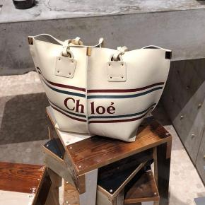 """Chloé logo shopper bag købt i juli 2019. Standen er som ny, da jeg har brugt den i begrænset omfang. Den fungerer super som bl.a. weekendtaske, da den er ganske rummelig. Der medfølger også en """"pung"""" inde i tasken, som sidder fast i snor. Nypris er 8195kr. BYD:)"""