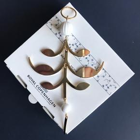 Ny palmette str. 12-13 cm fra Royal Copenhagen Christmas serien sælges. Udgået af RC's sortiment. Jeg har 3 stk tilbage men kun 1 æske fra RC og 2 neutrale æsker.  De er købt i USA og det er muligvis derfor, at æskerne er anderledes end dem man har kunnet få herhjemme.    Prisen er pr. Stk.