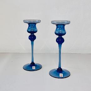 To stk Cassiopeia lysestager i safirblåt glas. Designet af Torben Jørgensen for Holmegaard Glasværk. Lyseholder og knop blæst i form, påsat langt udtrukket stilk og fod. Kraven varmt af sprængt. Højde: 22,8 cm. Diameter: 7,9-8,9 cm.
