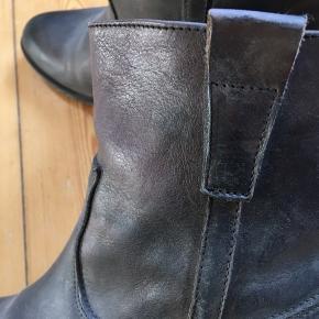 I originalæske. Stadig med prismærke. Er blevet forsålet hos skomager før taget i brug. Farve: sort med patina/støvet sort-grå. Man er altid velkommen til at prøve på før evt. køb