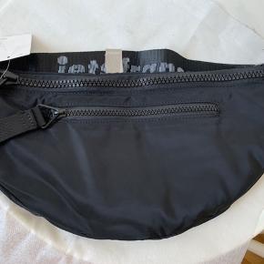 Sort unisex bæltetaske / bumbag fra Iets Frans / UO i stærkt poly / nylon. Regulerbar rem (knap 85 cm) med Iets Frans logo. Bredde øverst knap 35 cm Højde ca 17,5 cm To rum og lille lynlås lomme i det store rum Hvis afhent 150
