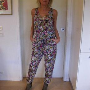 Sælger for veninde, denne yndige jumpsuit, med fine blomster,  Model: Lise sej med skrålommer og bindebånd i liv. Yderst velholdt 100pp