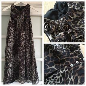 Cocktailkjole i leopard, super feminin festkjole i A-facon, med foer og med små stofroser på højre skulder. Yderkjole er 100% silke, brugt få gange. Længde bag på, fra skulder og ned, 90 cm. Bytter ikke!