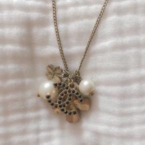 Smukkeste vintage halskæde fra Chanel med en masse fine charms. Tre små perler er faldet af bagsiden på Chanel logoet, men slet ikke noget man ser Flere billeder tages ikke. Prisen er umiddelbart fast.