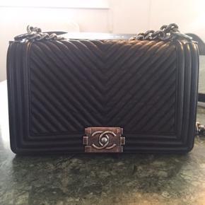 Super smuk Chanel Boy taske. Herringbone, blåsort farve. Old medium.  Tasken er købt i Paris 2015.  Kvittering haves. Æske, dustbag følger med.  En lille smule slid på hjørnerne af tasken, men ellers i super fin stand. Prisen er sat derefter.