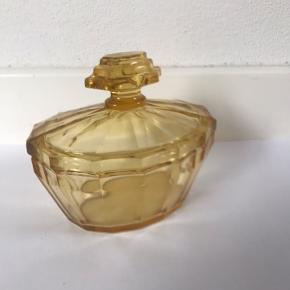 Lige fin glaskrukke med låg til opbevaring af smykker og andre nips. Har to små skader på låget derfor kun 75kr